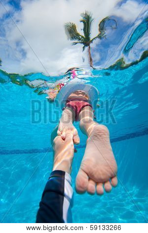 Father holding his little daughter feet while she swims