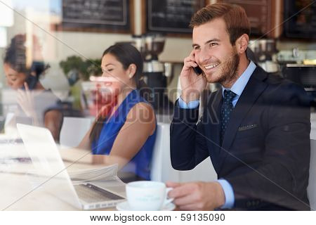Businessman Using Mobile Phone And Laptop In Coffee Shop