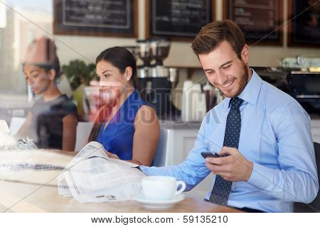 Businessman With Mobile Phone And Newspaper In Coffee Shop