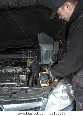Auto mechanic measuring car battery voltage using multimeter