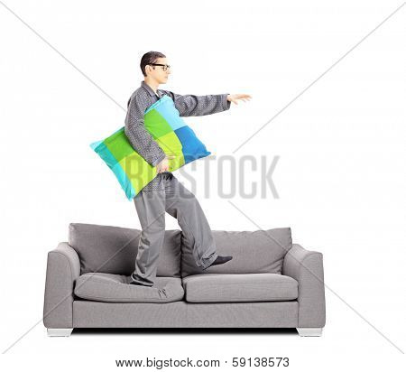 Full length portrait of guy in pajamas sleepwalking on sofa, isolated on white background