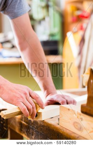 Carpenter working on wooden workpiece in his workshop or carpentry