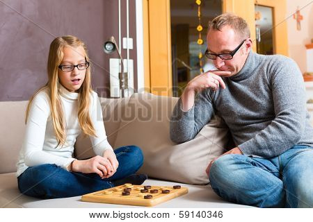 Father and daughter playing parlor or board game checkers on sofa