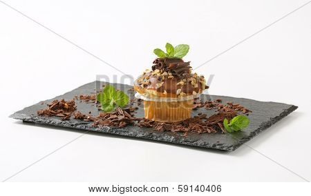 fresh home made muffin with chocolate curls on a slate cutting board