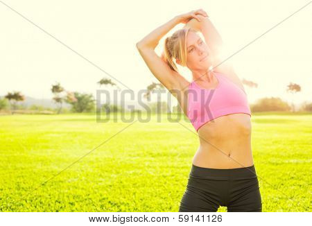 Attractive fit young woman stretching before exercise workout, sunrise early morning backlit. Healthy lifestyle sports fitness concept.