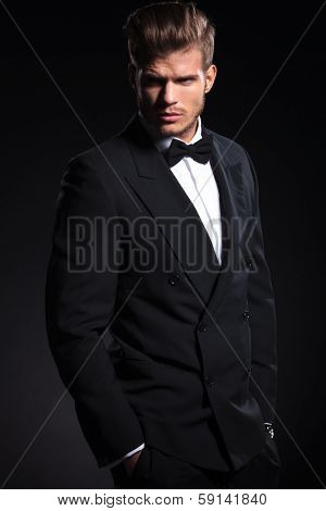 side view of a fashion man in tuxedo looking away from the camera