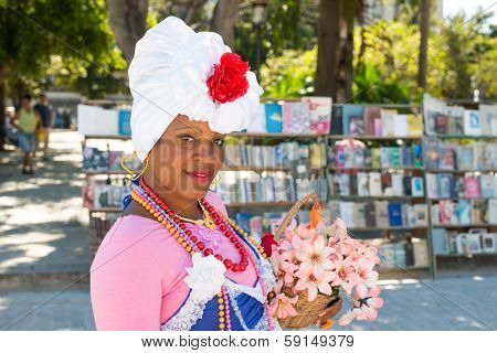 HAVANA,CUBA - JANUARY 20, 2014:Beautiful young latin woman dressed with colorful typical clothes holding a flower basket.Characters like this are common in the streets of Old Havana