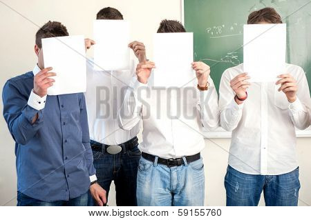 Highschool boys holding white papers in front of their heads