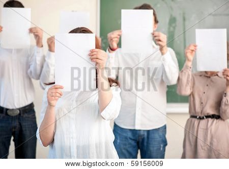 Group of students with blank white papers in front of heads