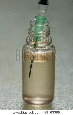 a syringe in a bottle of vaccination serum