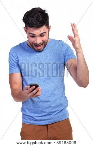 excited young casual man looking shocked by the good news he is reading on his phone