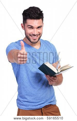young student reading a good book and making the ok thumbs up hand sign