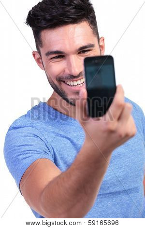 smiling young man taking his own picture with his smart phone on white background