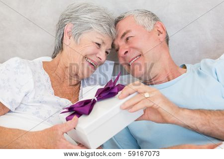 Happy senior couple exchanging gift box while relaxing in bed at home