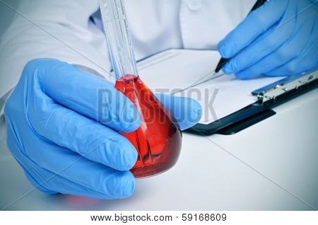 man in white coat with a volumetric flask with a red liquid in a laboratory