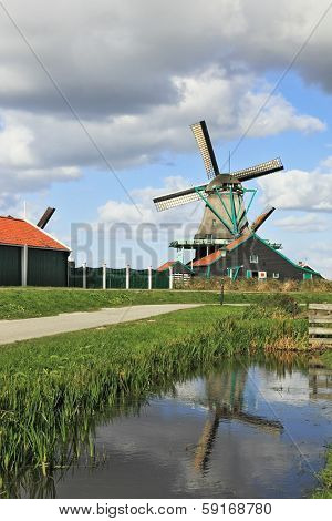 The village - an ethnographic museum in Holland. The picturesque windmill and a barn is reflected in smooth water of the channel