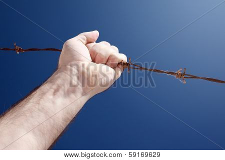 A barbed wire with a hand against the blue sky