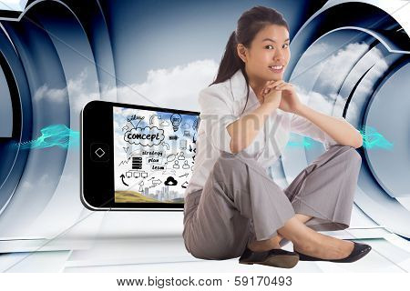 Smiling businesswoman sitting with hands together against abstract blue cloud design in futuristic structure