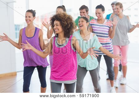 Portrait of cheerful fitness class and instructor doing pilates exercise in bright room