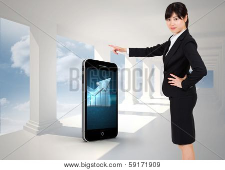 Businesswoman pointing against bright white hall with columns
