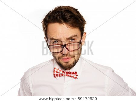 Old-fashioned nerdy businessman wearing a red and white polka dot bow tie looking over the top of his glasses with a sceptical assessing look, isolated on white
