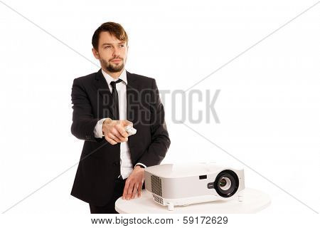 Businessman using a projector for a presentation or doing in house corporate training aiming the remote control as he changes the slide, isolated on white