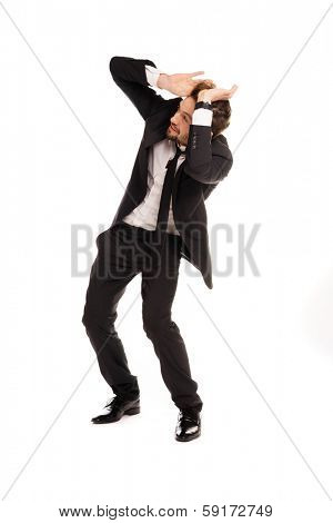 Stylish businessman cowering in fear with his hands raised to protect his head leaning backwards, isolated on white