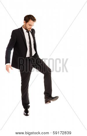 Businessman in a stylish suit raising his foot to stamp on something , isolated on white