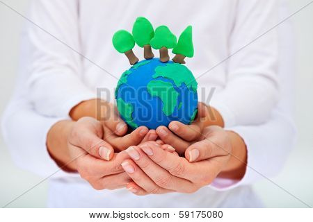 Protecting our environment concept - clay earth with trees held by child and adult hands