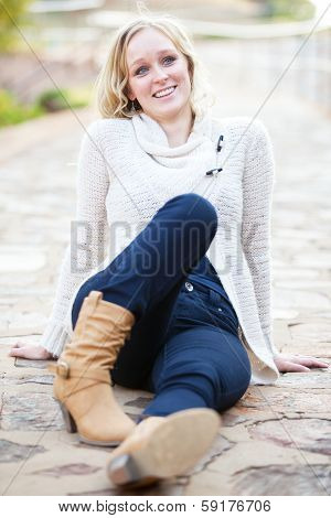 Smiling Young Blonde Woman Relaxing On Pavement