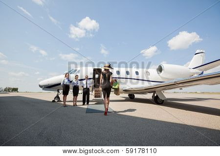 Rear view of rich woman walking towards private jet while pilot and stewardesses standing at airport terminal