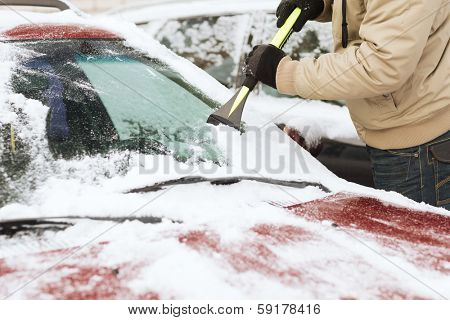 transportation, winter and vehicle concept - closeup of man scraping ice from car windshield with brush