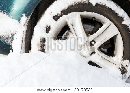 transportation, winter and vehicle concept - closeup of car wheel stuck in snow