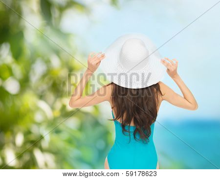 vacation and summer holidays concept - model in swimsuit with hat