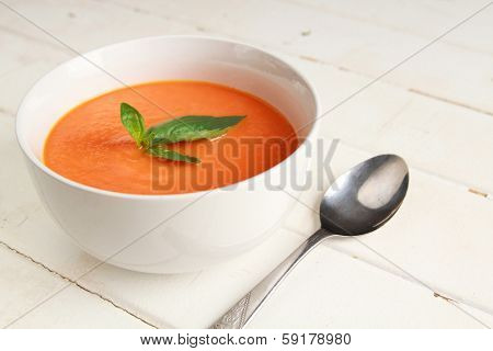 Carrot soup in a white bowl on a white wooden background
