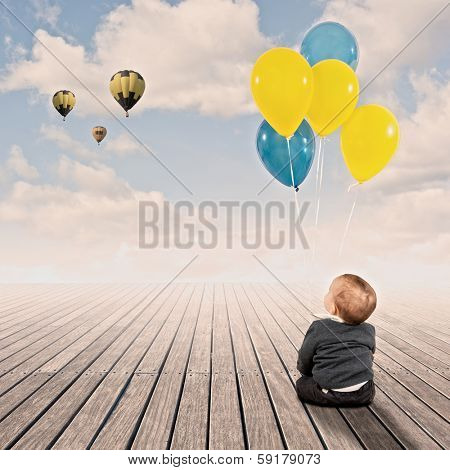 baby boy holding bunch of balloons on a wharf