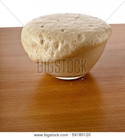 Rising Yeast Dough in bowl on wooden table  Isolated on White Background