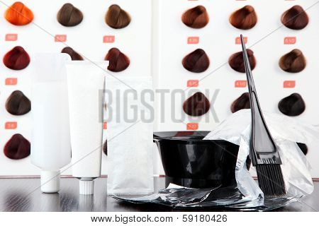 Hair dye kit and hair samples of different colors, on wooden table, on light background