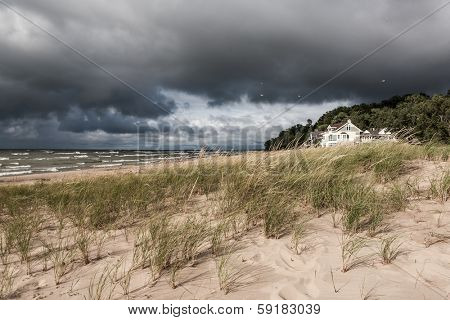 Dune grasses and vacation homes with storm clouds
