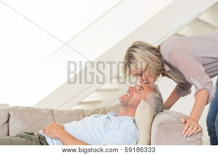 Side view of a woman kissing a relaxed mature mans forehead in the living room at home