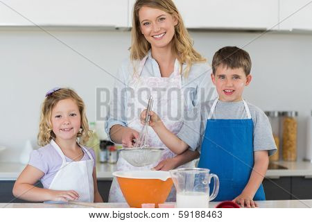 Portrait of mother with son and daughter baking cookies at counter top in kitchen