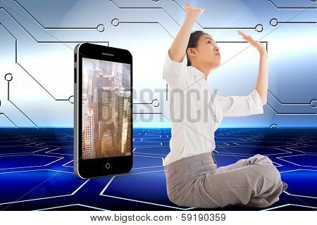 Businesswoman sitting cross legged pushing up against technological background