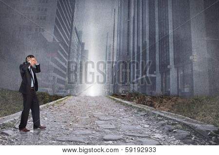 Stressed businessman with hands on head against cityscape projection above stony path