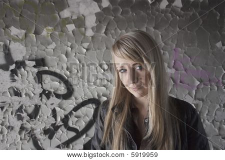 Female Model Standing At Old Painted Wall