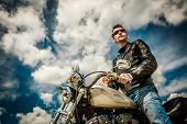 image of biker  - Biker man wearing a leather jacket and sunglasses sitting on his motorcycle looking at the sunset - JPG