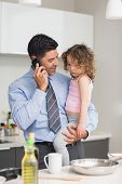 Well dressed father with daughter preparing food while on call in the kitchen at home