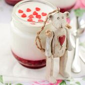 Teddy Bear Toy Leaning Over A Jar Of Yoghurt With Raspberry Jam