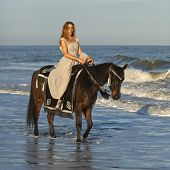 stock photo of bareback  - woman in medieval dress on horseback in ocean - JPG