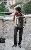 MOSTAR, BOSNIA AND HERZEGOVINA - AUGUST 9, 2012: Street musician plays accordion. The streets of Mos