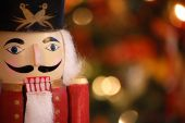image of nutcracker  - A classic wooden nutcracker with Christmas lights in the background - JPG